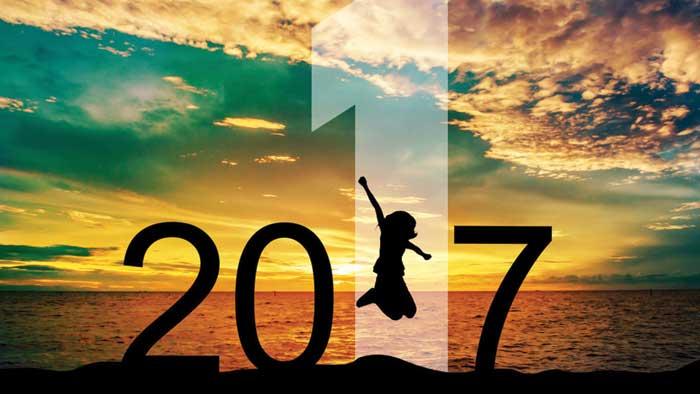 Girl jumping at sunset welcoming New Year 2017