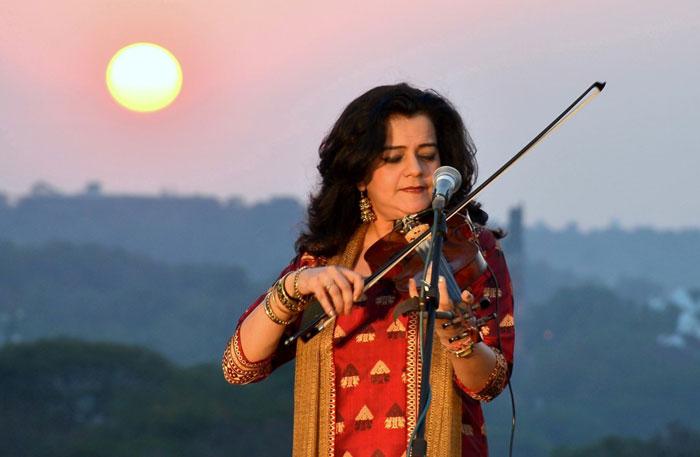 Sunita Bhuyan playing the violin at sunset
