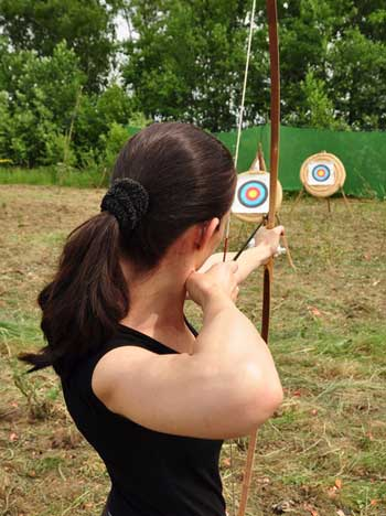 Young girl aiming a bow and arrow at a target