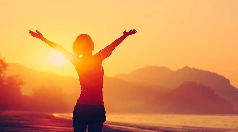 Woman raising hands towards sunset