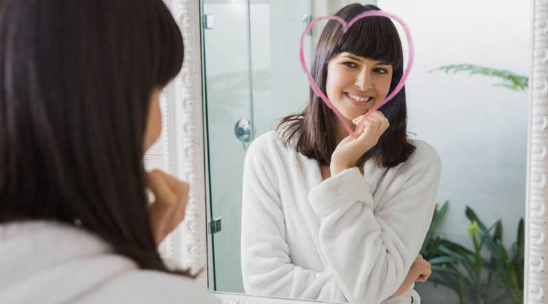 Young woman looking in the mirror at a heart shape drawn around her face