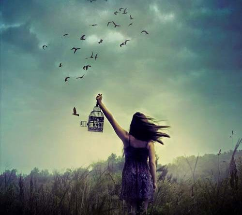 Girl holding open a cage to let birds fly free