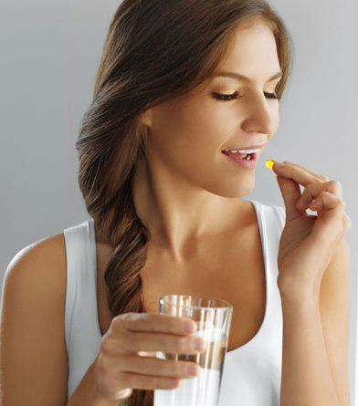 Young woman taking a fish supplement pill