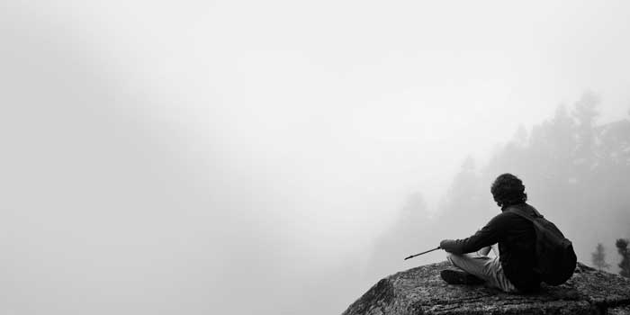 Man sitting on a misty mountaintop