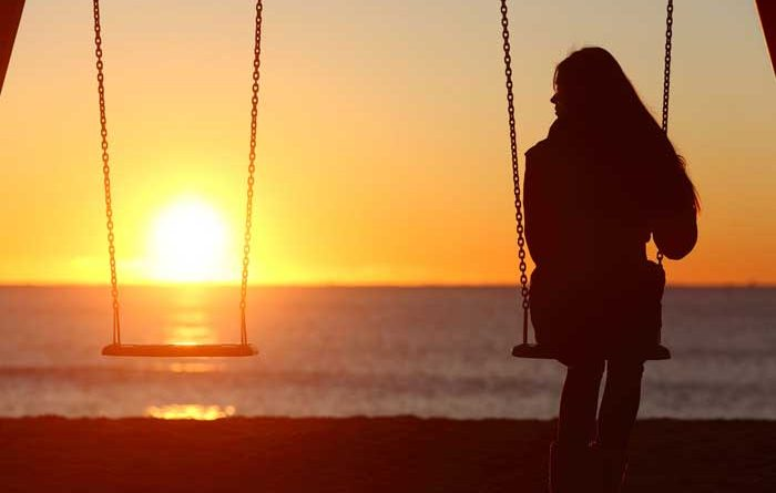 Girl sitting on a swing at sunset with an empty swing beside her