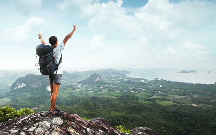 Man standing victoriously on top of a mountain