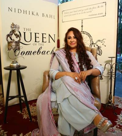 Nidhika Bahl seated in front of her book The Queen Of The Comeback