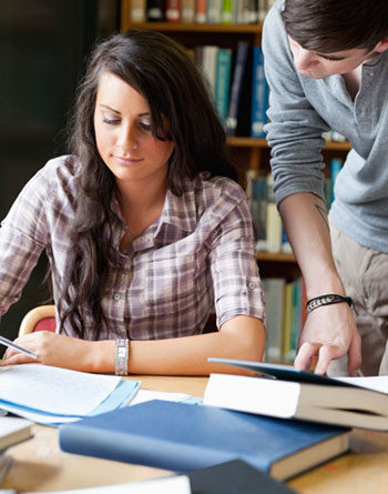 Female and male student studying together in a library