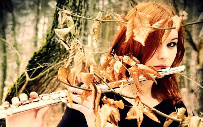 Woman playing the flute with autumn leaves around