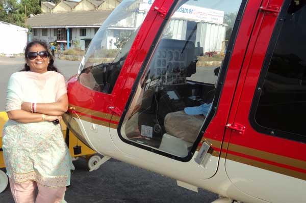 Leena Juvekar Duttagupta near Adonis Aviation helicopter