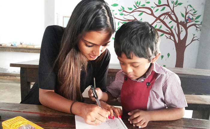 Girl teaching young child as part of community service