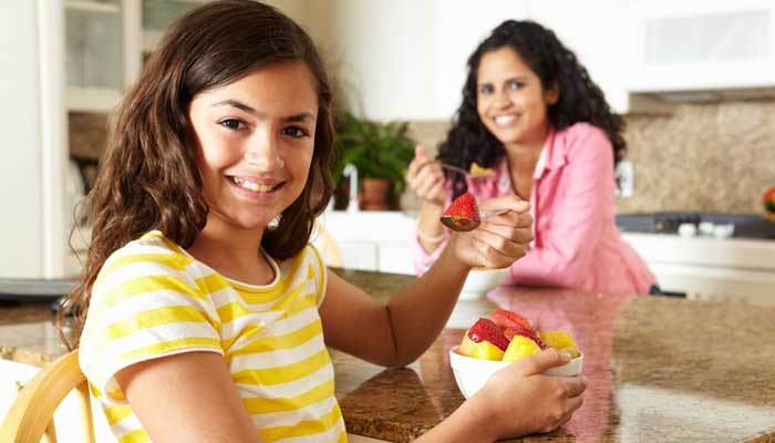 Teen girl having breakfast in the kitchen with her mother