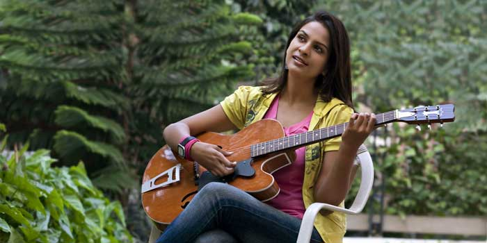 Young woman sitting in a garden and playing the guitar