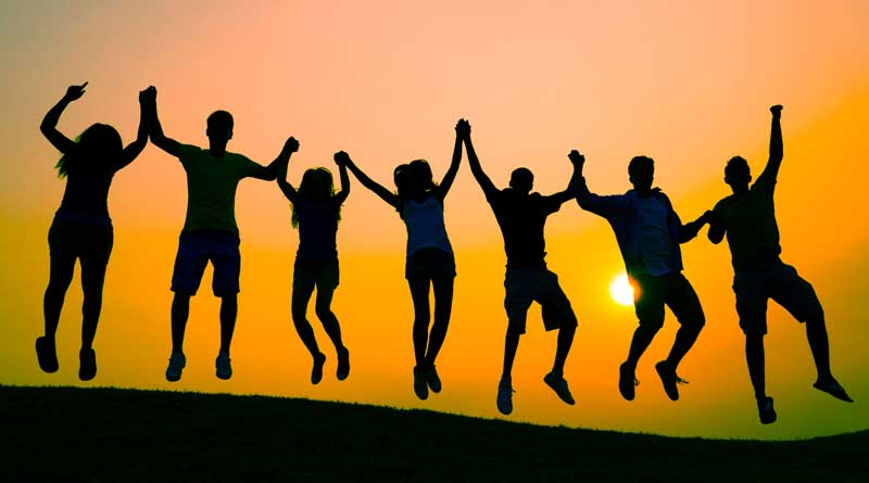 Silhouettes of youth jumping at sunset