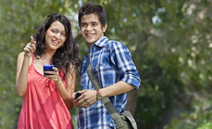 Male and female college friends looking up from cell phones and smiling