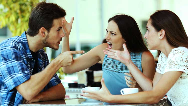 Two female and one male friend arguing at a table