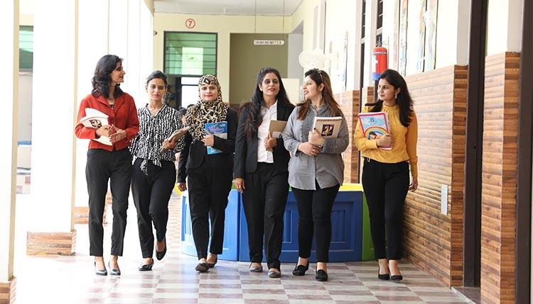 Group of teachers walking down school corridor