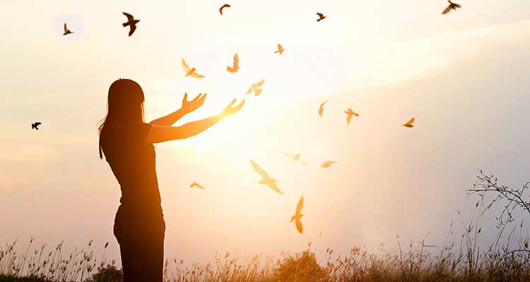 Woman standing with her arms outstretched at sunset with birds flying around