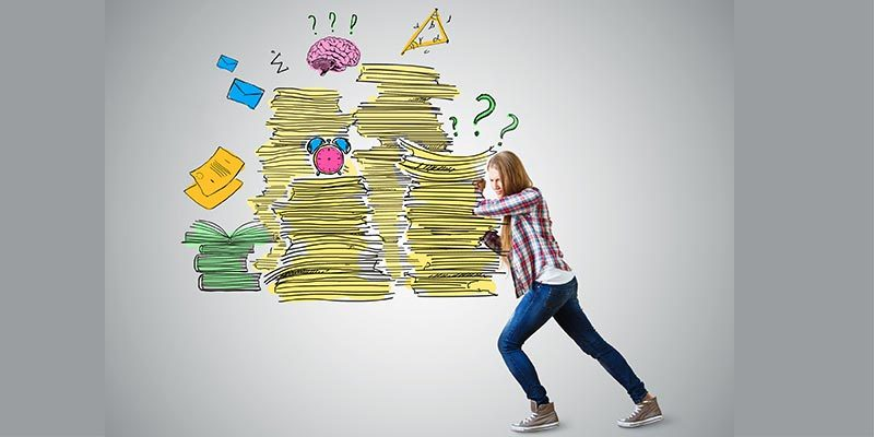 Girl pushing away a stack of papers and other work