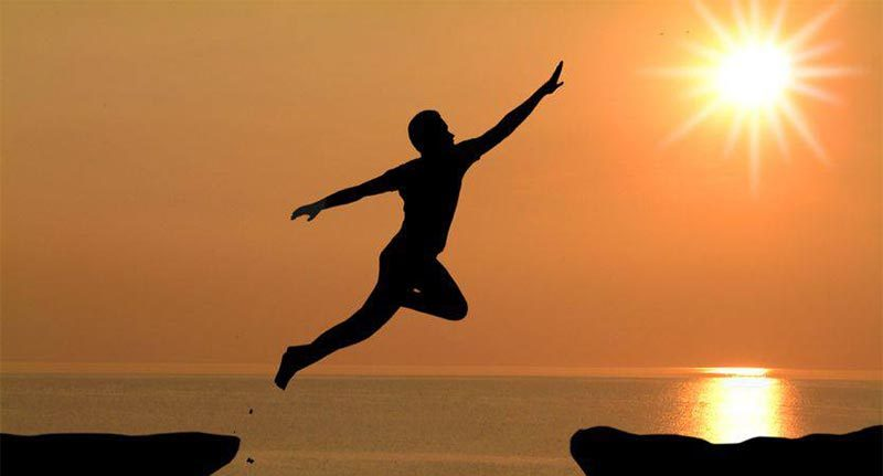 Man leaping from one rock to another reaching for the sun