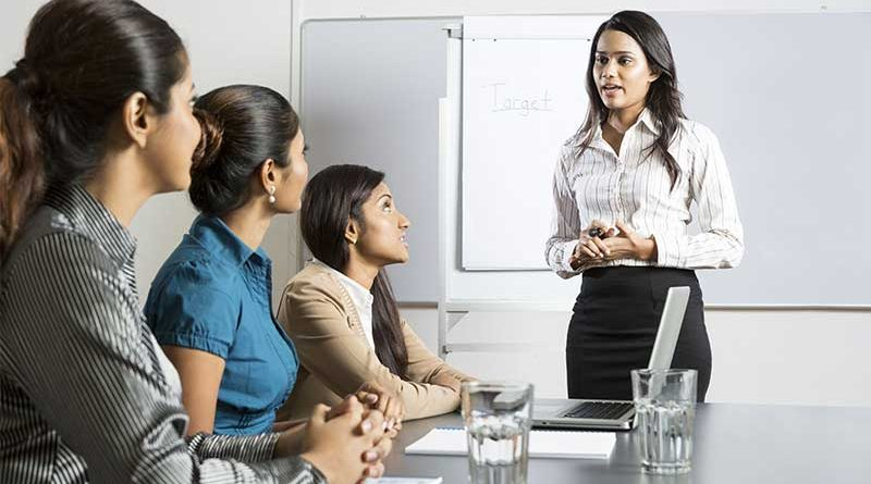 A young woman giving a presentation to three other women