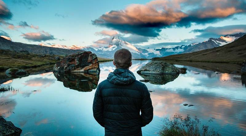 Man looking out over a calm lake