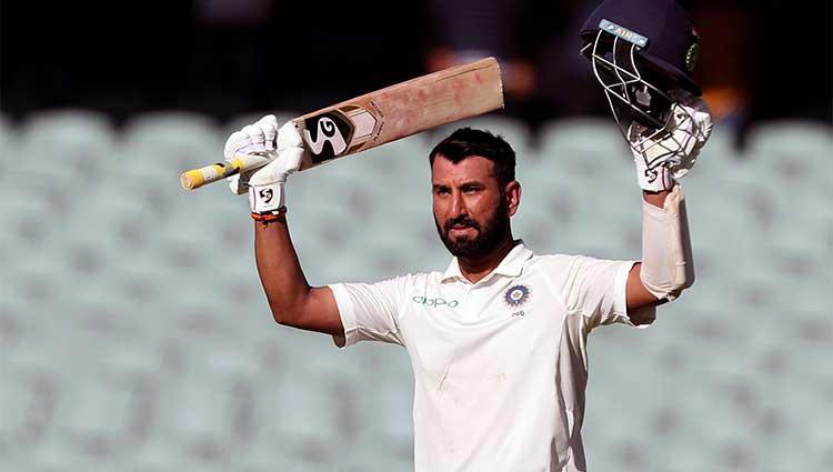Cheteshwar Pujara lifting his arms up in celebration