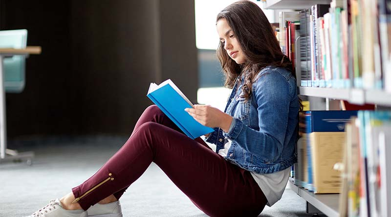 Young girl reading a book in a library