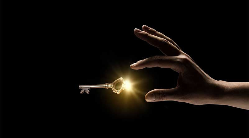 Hand reaching out for glowing golden key