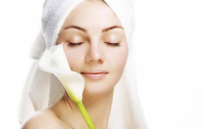 Woman wearing a towel over her hair placing a flower against her facial skin