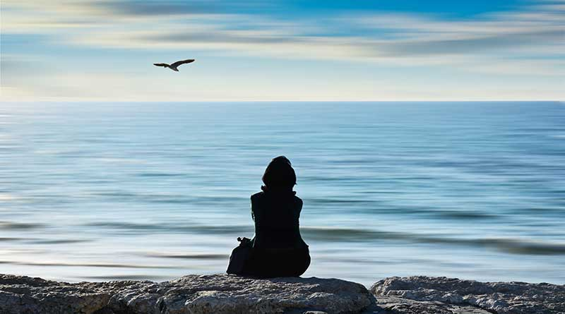 Lonely girl sitting on the rocks by the sea as a seagull flies overhead