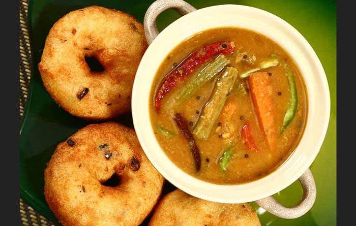Bowl of sambar with three wadas alongside