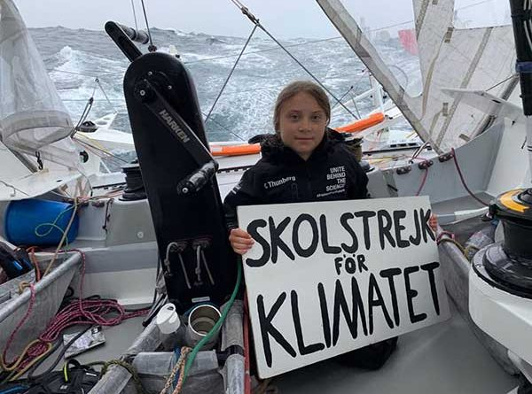 Greta Thunberg holds up a sign on board the Malizia II
