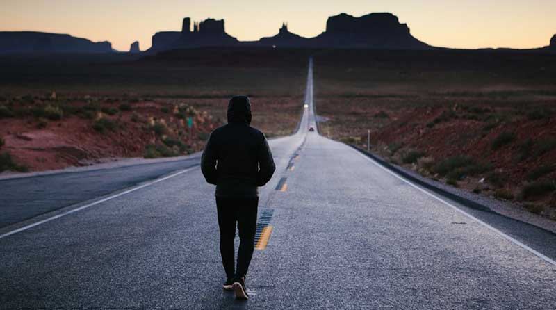 Young man walking down a road into the distance