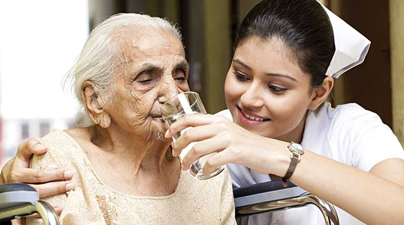 Nurse helping old woman to drink water