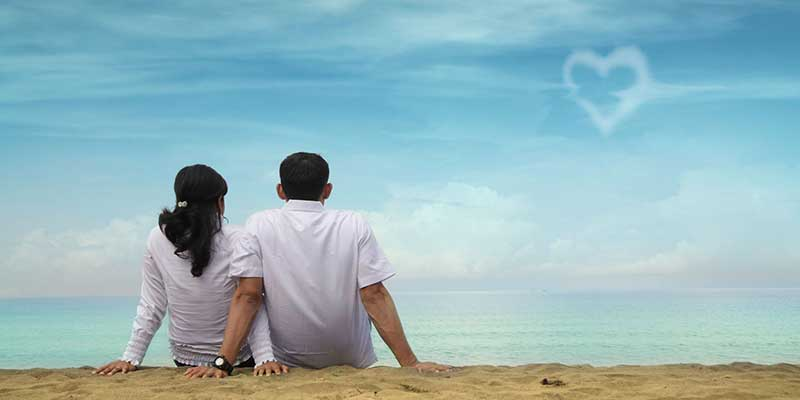 Couple on a beach looking at a heart sign in the clouds