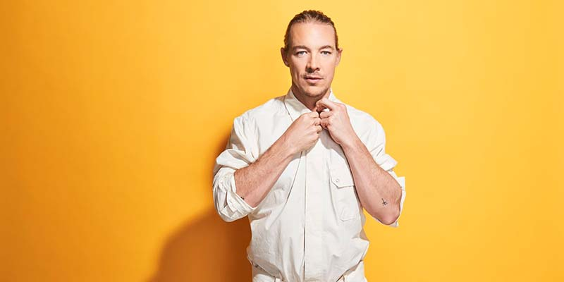 Diplo standing against a yellow background
