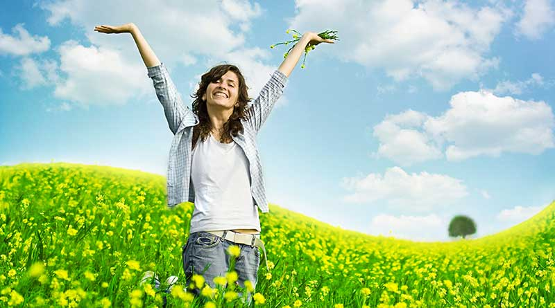 Happy young woman in a field of yellow flowers