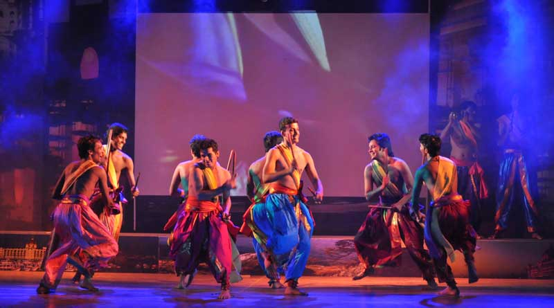 Male dancers performing the Kolattam Dance on stage