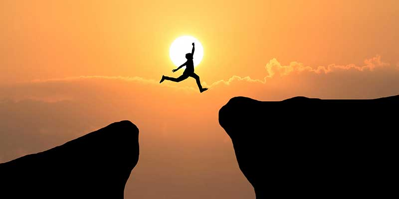 Man leaping from one cliff to another at sunset