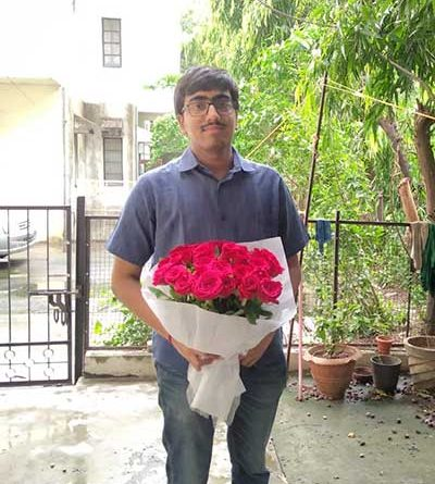 Chaitanya Iyer standing with a bouquet of roses