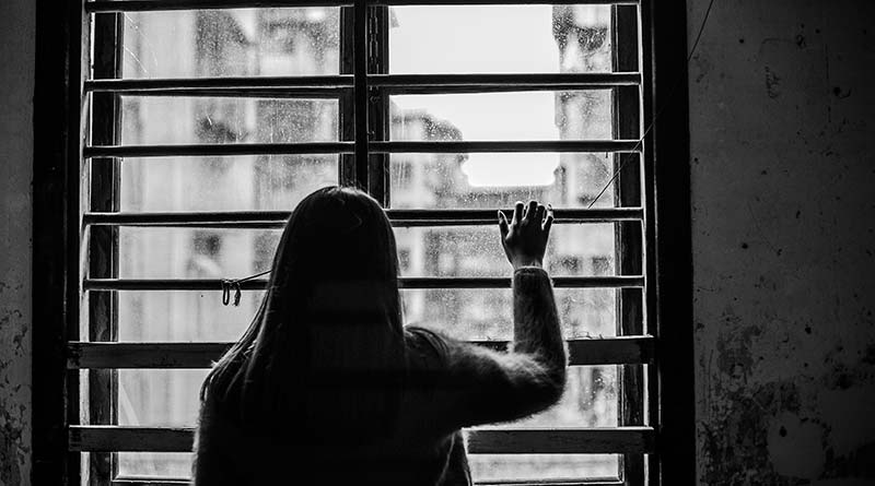 Depressed girl standing and looking out of a window
