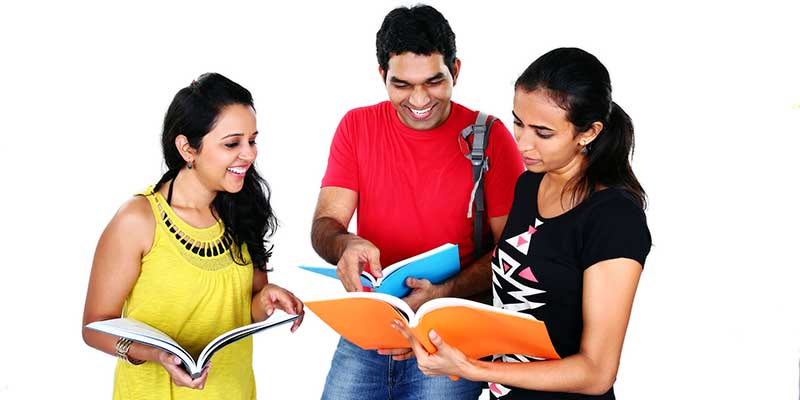 Two female and one male friend smiling and studying