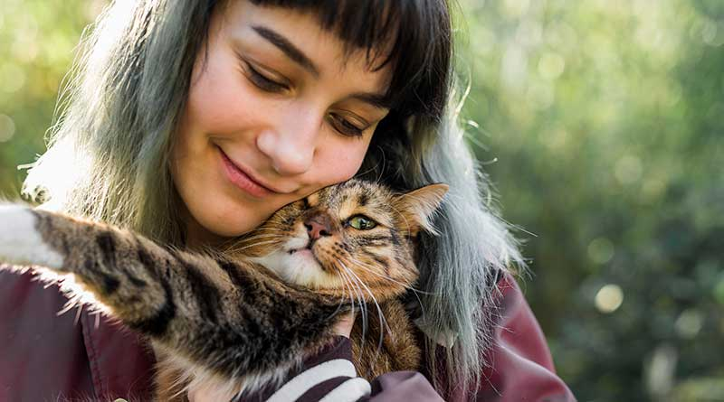 Girl holding a cat close to her face