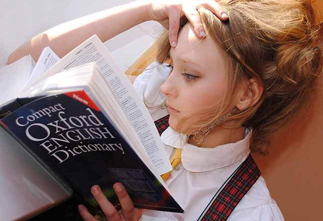Young girl reading a dictionary