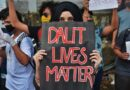 Young woman protesting with a Dalit Lives Matter poster