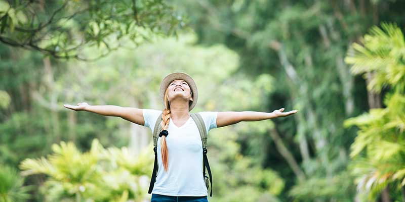 Young happy woman with arms raised in gratitude enjoying nature