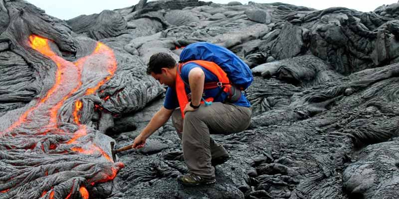 Geologist looking at lava from volcano