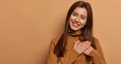 Cheerful young woman with hands over her heart in gratitude