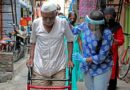 Young woman helping an elderly man to walk